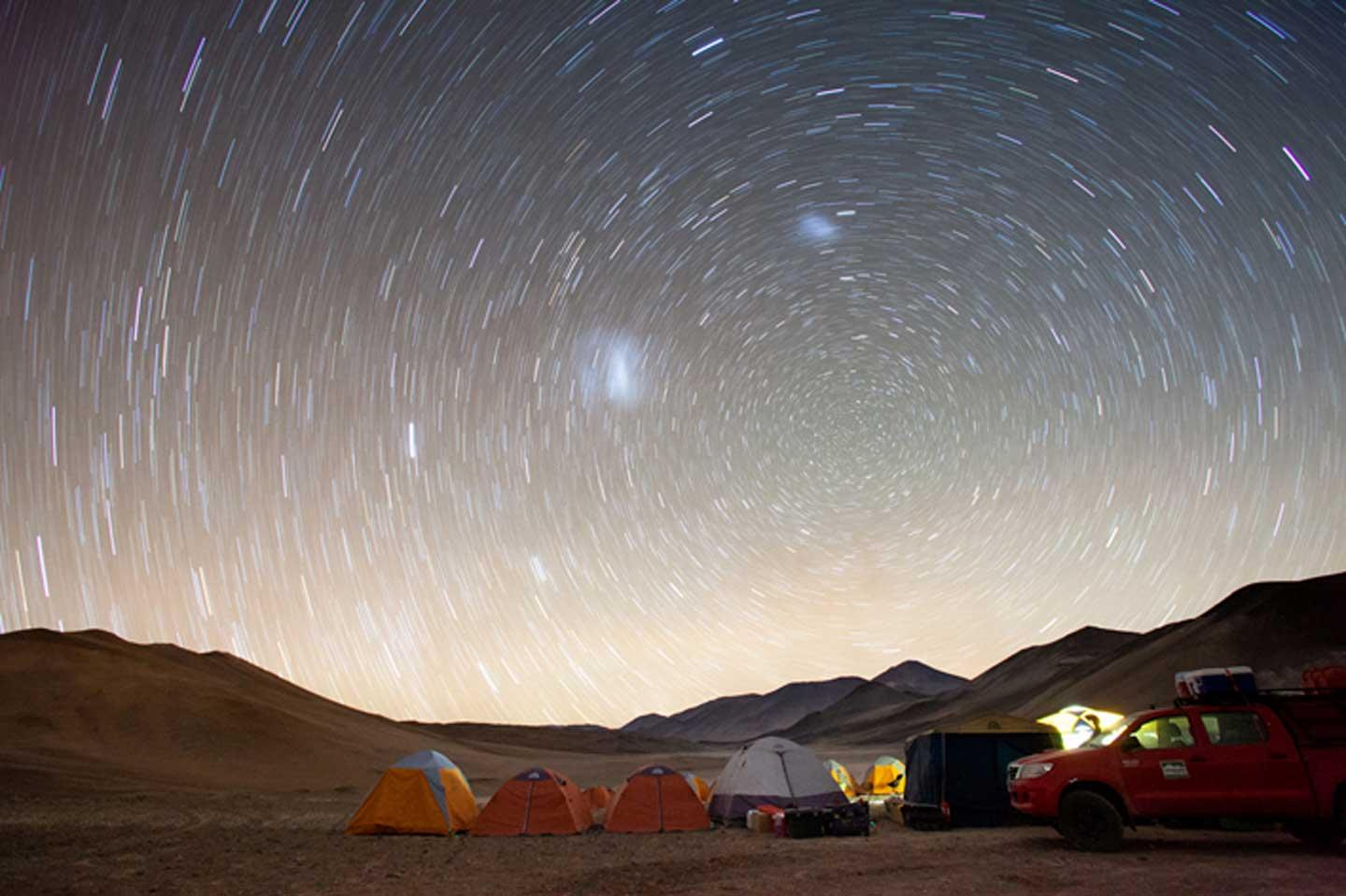 The Andes field expedition team's camp at night. Right in the center of the star trail, the two Magellanic Clouds give visions of alien worlds. Photo credit: Victor Robles, Campoalto and the SETI Institute NAI Team. Image credit: None