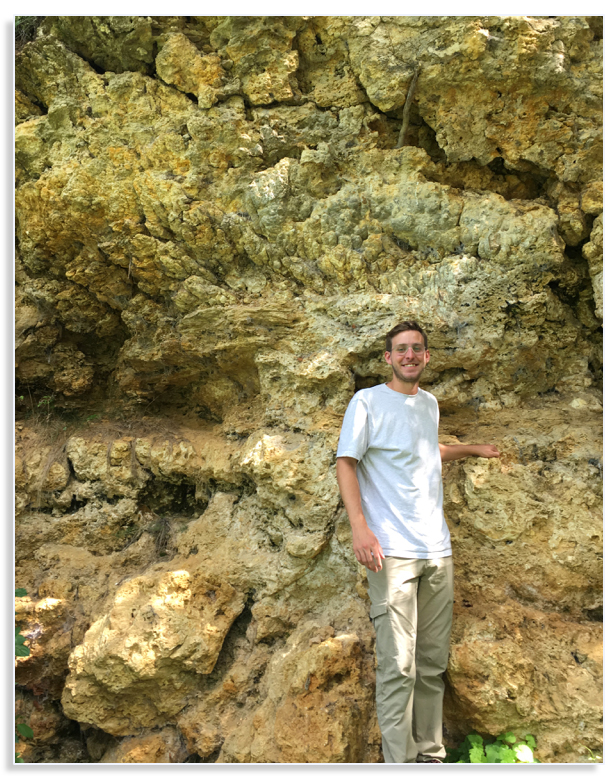 Chris Tino poses in front of a massive outcrop of fossil lacustrine microbialites in Nördlinger Ries crater, Germany. Source: UCR Image credit: UCR