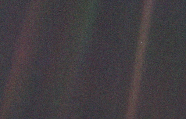 "The iconic ""pale blue dot"" image of Earth taken by the Voyager 1 spacecraft, from a distance of 3.7 billion miles in 1990. Earth is the speck halfway down the brownish streak to the right. The streaks are artifacts, caused by the scattering of sunlight in the probe's optics. Image credit: NASA"