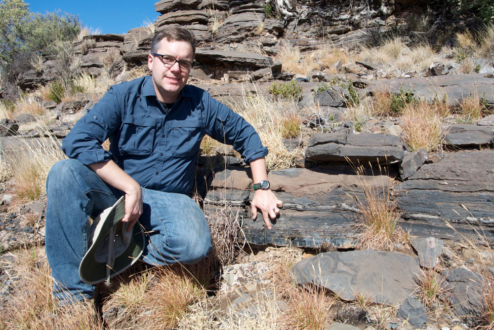 Andrew Czaja indicates the layer of rock from which fossil bacteria were collected on a 2014 field excursion near the town of Kuruman in the Northern Cape Province of South Africa. Source: Aaron Satkoski Image credit: None