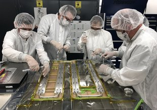 Technicians and engineers work together on Sept 12, 2019, to bond thermal tubing to a panel built for NASA's Europa Clipper spacecraft. The tubing controls the orbiter's temperature as it travels.