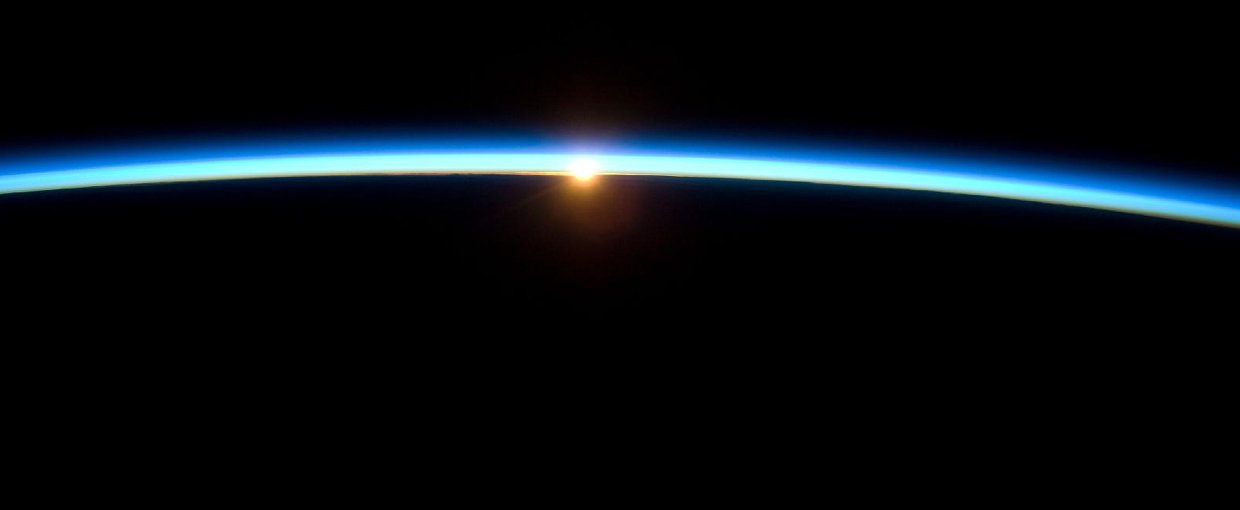 The thin line of Earth's atmosphere and the setting sun are featured in this image photographed by the crew of the International Space Station while space shuttle Atlantis on the STS-129 mission was docked with the station.