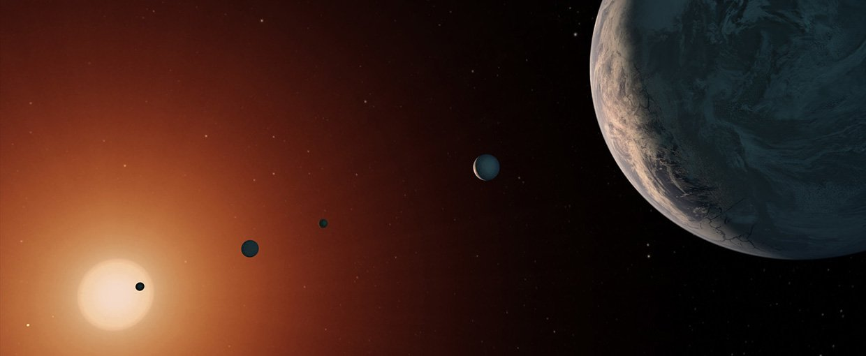 This illustration shows what the TRAPPIST-1 system might look like from a vantage point near planet TRAPPIST-1f (at right).