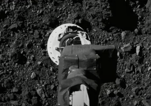 Image from OSIRIS-REx at approximately 420 feet (128 meters) above the surface of Bennu. The spacecraft's sampling arm – called the Touch-And-Go Sample Acquisition Mechanism (TAGSAM) – is visible in the lower part of the frame.