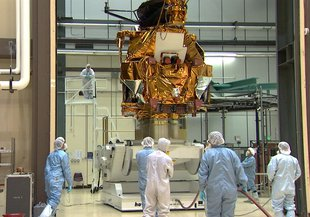 A group of engineers and technicians watch as the Mars Reconnaissance Orbiter is lifted in a cleanroom at Lockheed Martin in Littleton, Colorado during the orbiter's assembly, test and launch operations phase.