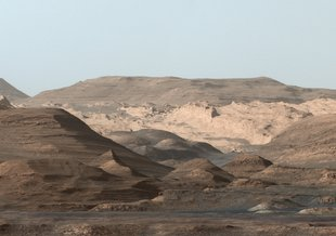 This composite image looking toward the higher regions of Mount Sharp was taken on September 9, 2015, by NASA's Curiosity rover. In the foreground - about 2 miles (3 kilometers) from the rover - is a long ridge teeming with hematite, an iron oxide.