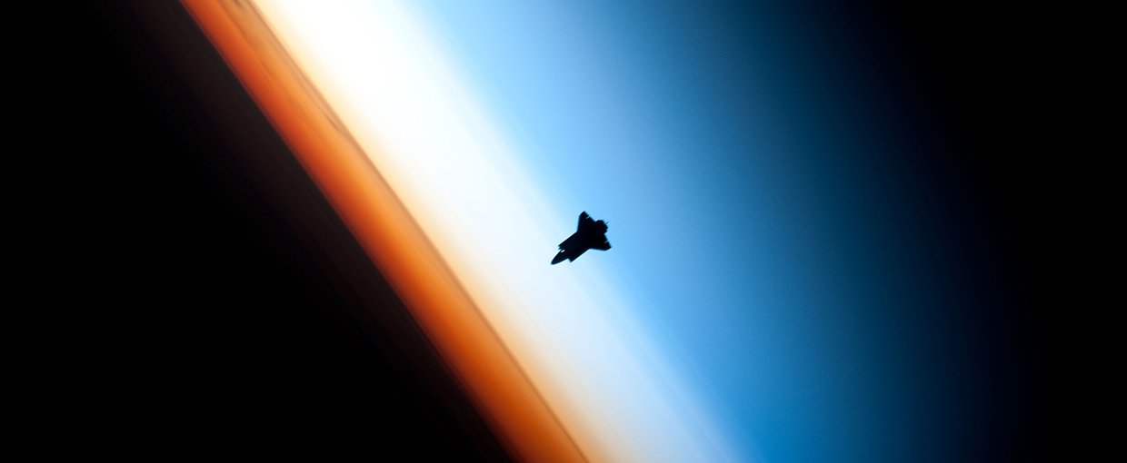 The space shuttle Endeavour hangs against Earth's atmosphere. The stratosphere is represented by the whitish layer.