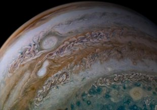 This view of Jupiter's atmosphere from NASA's Juno spacecraft includes something remarkable, two storms caught in the act of merging.