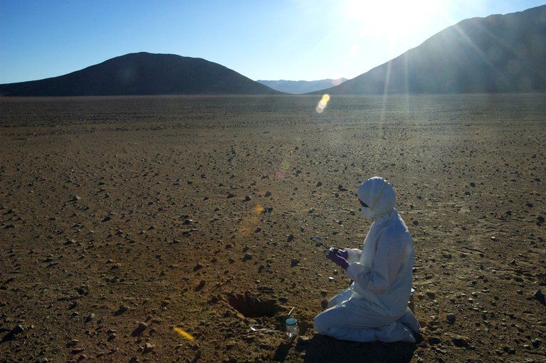 "The Atacama desert is one of the driest places on Earth, making it a good Mars analogy. A scientist searching for signs of life (""biomarkers"") in the soil must use clean suits, gloves, masks, goggles, and sterile tools to make sure no contamination ends up in the sample.  Image credit: Alfonso Davila/SETI Institute"