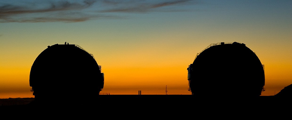 A silhouetted view of the Keck telescopes at sunset.