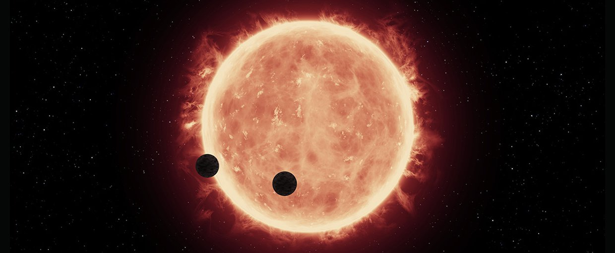 Artist's illustration of two Earth-sized planets, TRAPPIST-1b and TRAPPIST-1c, passing in front of their parent red dwarf star, which is smaller and cooler than our sun. NASA's Hubble Space Telescope looked for signs of atmospheres around these planets.
