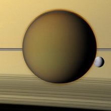 Saturn's third-largest moon Dione can be seen through the haze of its largest moon, Titan, in this view of the two posing before the planet and its rings from NASA's Cassini spacecraft.