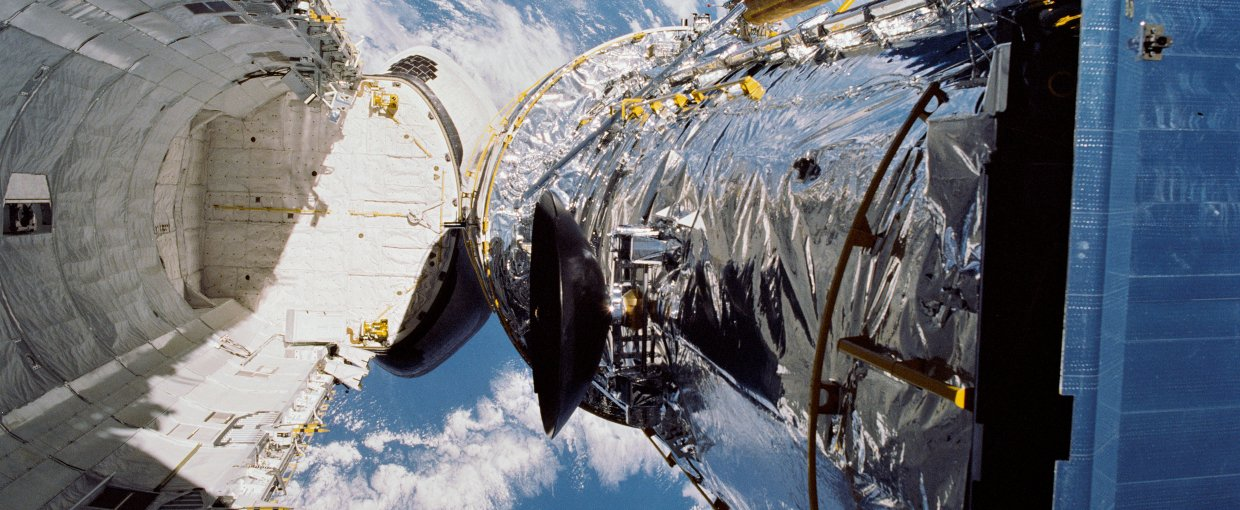 In this April 25, 1990, photograph taken by the crew of the STS-31 space shuttle mission, the Hubble Space Telescope is suspended above shuttle Discovery's cargo bay some 332 nautical miles above Earth. Credit: NASA