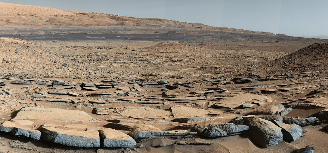 "A view from the ""Kimberley"" formation on Mars taken by NASA's Curiosity rover. The strata in the foreground dip towards the base of Mount Sharp, indicating the ancient depression that existed before the larger bulk of the mountain formed."