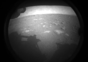 This is the first imager NASA's Perseverance rover sent back after touching down on Mars on Feb 18, 2021. The view, from one of Perseverance's Hazard Cameras, is partially obscured by a dust cover.