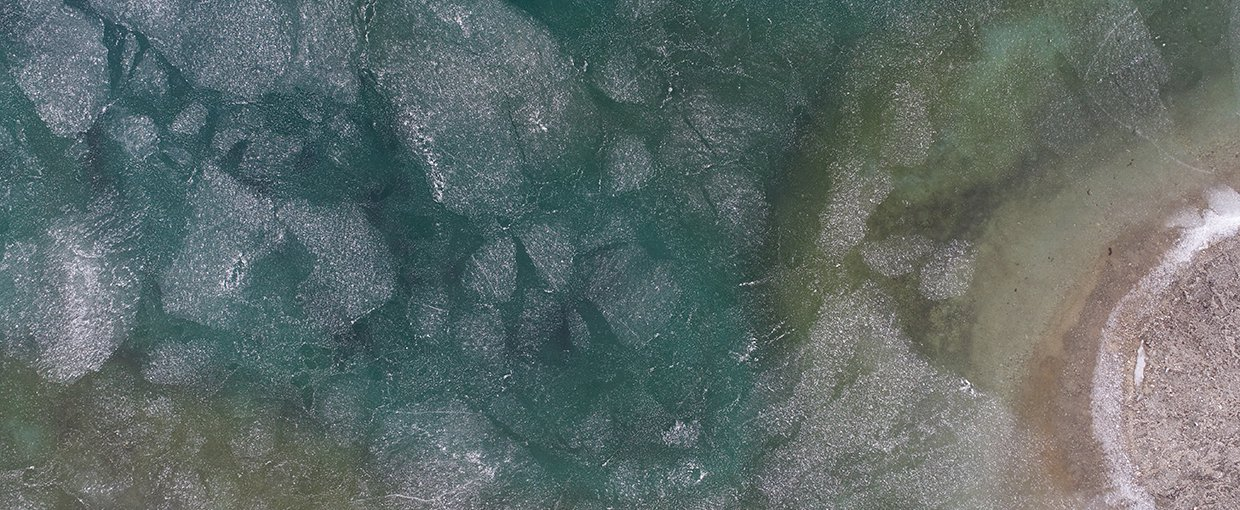 An icy lake in Svalbard, Norway, taken by an unmanned aerial vehicle. Life on Earth may have begun in an environment with both water and ice, and modern analogs may help the scientific community understand how.