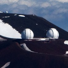 An arial shot of the twin Keck telescopes on a bright winter day on the snow capped summit of Mauna Kea.