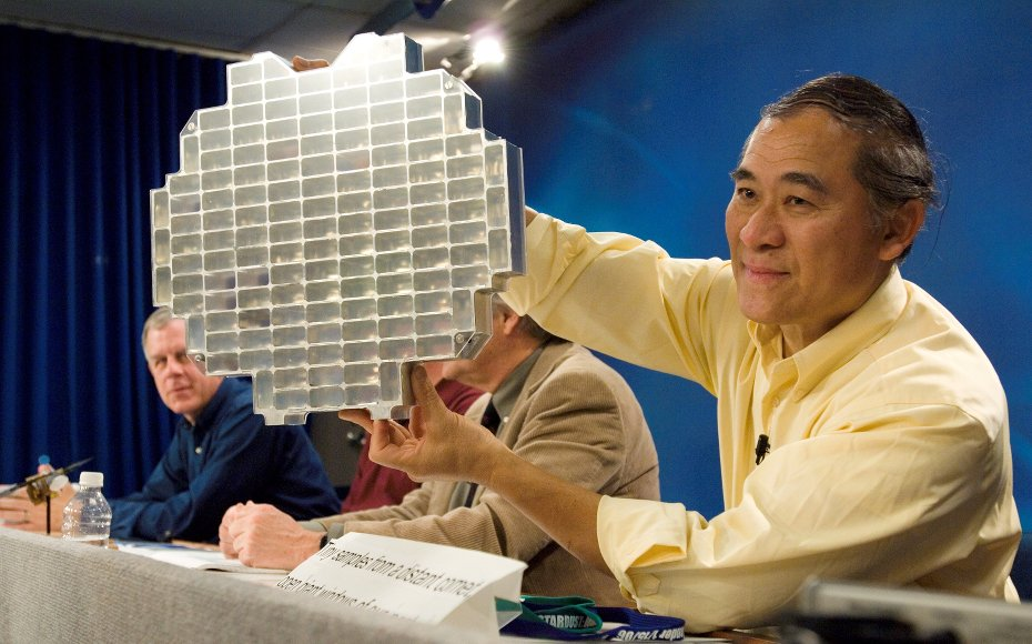 Dr. Peter Tsou, Stardust deputy principal investigator, holds a Stardust sample tray while speaking to various news media representatives during a press conference at Johnson Space Center.