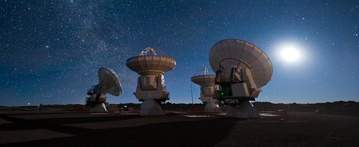 Four antennas of the Atacama Large Millimeter/submillimeter Array (ALMA) gaze up at the star-filled night sky.