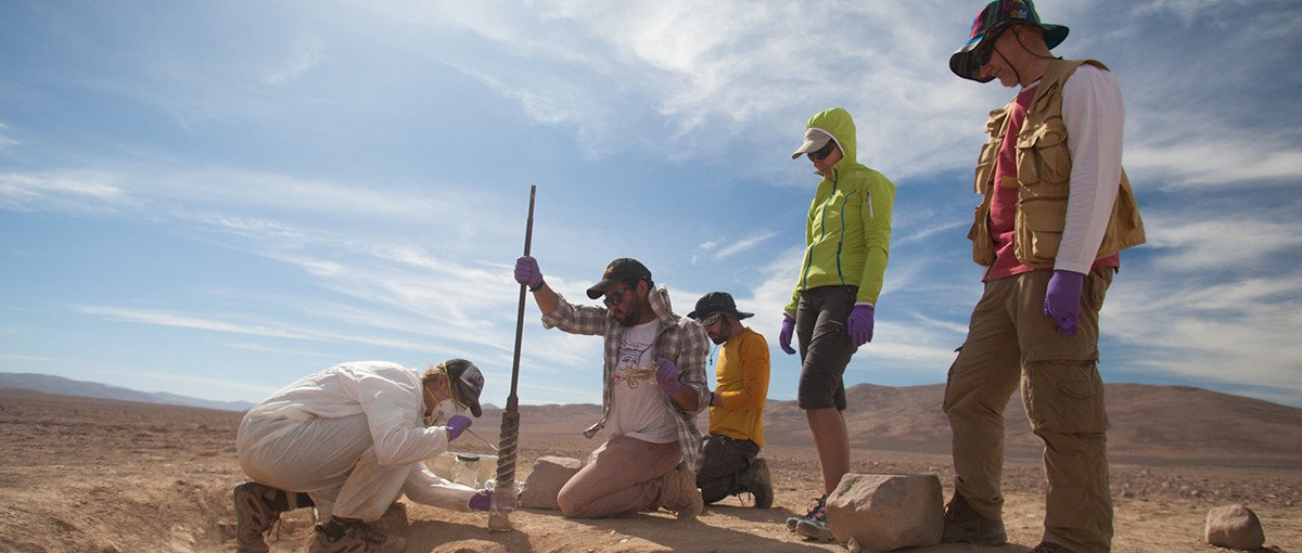 Mary Beth Wilhelm of NASA Ames Research Center, wearing the white suit, tests samples obtained from an excavation pit in Chile's Atacama Desert. On the right are Miriam Villadangos and Victor Parro of the Centro de Astrobiología.