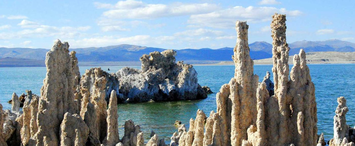 "Mono Lake, California, with salt pillars known as ""tufas"" visible. JPL scientists tested new methods for detecting chemical signatures of life in the salty waters here, believing them to be analogs for water on Mars or ocean worlds like Europa. Image Credit: Mono County Tourism"