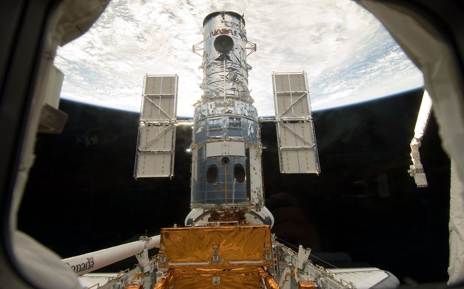 The Hubble Space Telescope stands tall in the cargo bay of the Space Shuttle Atlantis following its capture and lock-down in Earth orbit. Credit: NASA