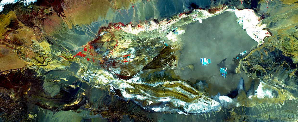 Landsat 7 image of Salar de Atacama from March 21, 2002. The Salt Pan is mostly a grey-green with some white and cyan. Bare ground and rock range from tan and brown to green and dark grey. Snow is white and vegetation is red.